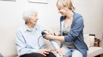 Verpleegkundige meet bloeddruk van oudere vrouw